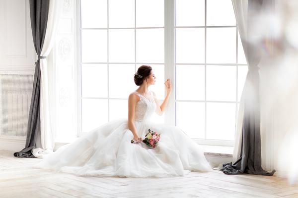 Braut sitzt im Prinzessinnen Brautkleid vor dem Fenster
