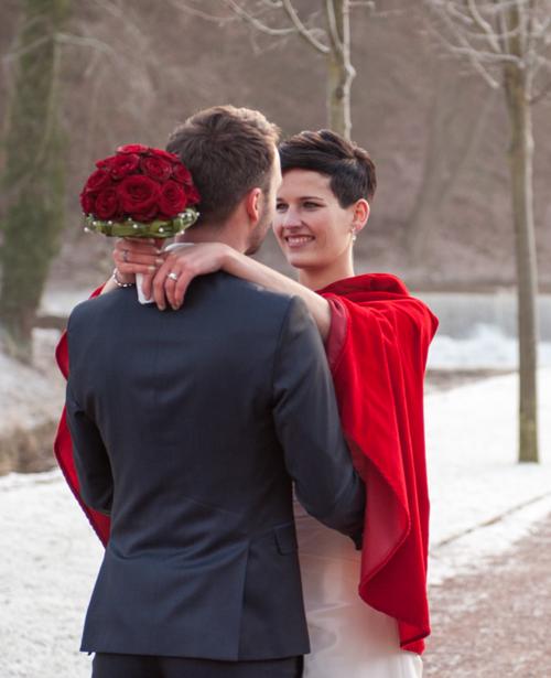 Brunette Braut mit Winter Hochzeitskleid und roter Brautjacke
