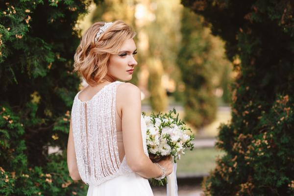 Blonde Braut in wunderschönen Vintage Brautkleid im Park