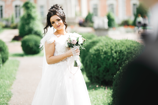 Schöne Braut im weißen Brautkleid mit Federn